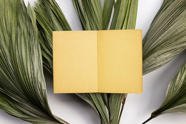 Braunes altes vintage-seitenpapier auf tropischen palmtrockenblättern.