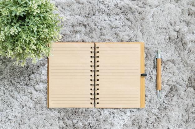 Braunes anmerkungsbuch der nahaufnahme mit braunem stift auf grauem gewebe capet maserte hintergrund