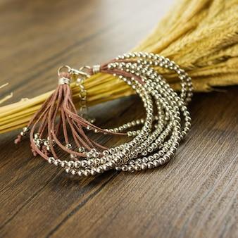Braunes armband mit mehreren strängen und trockenem gras