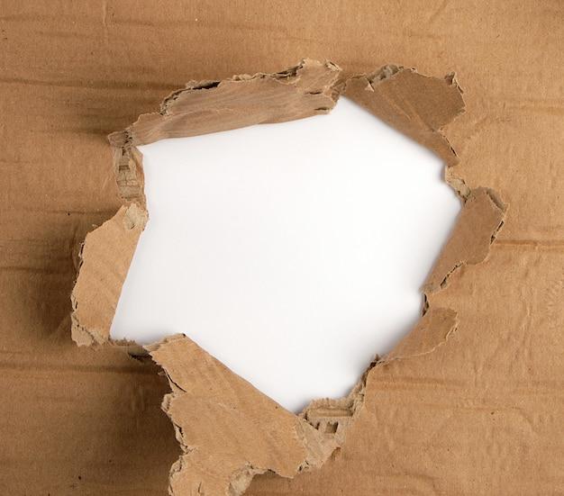 Braunes blatt papier mit einem loch, bildfüllend