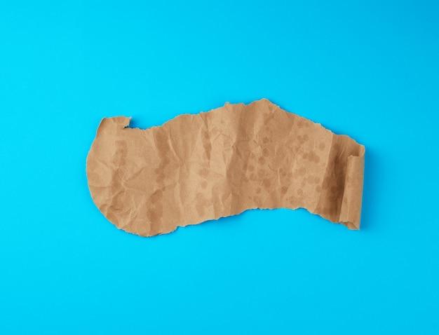 Braunes blatt papier mit mutigen stellen und einer wirbelnden ecke auf einer blauen oberfläche