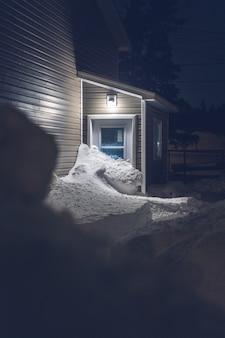 Braunes holzhaus bedeckt mit schnee während der nachtzeit
