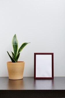 Braunes holzrahmenmodell im hochformat mit einem kaktus in einem topf auf dunklem arbeitsbereichstisch und weißem hintergrund