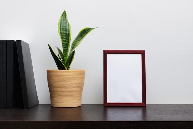 Braunes holzrahmenmodell im hochformat mit einem kaktus in einem topf und buch auf dunklem arbeitsbereichstisch und weißem hintergrund