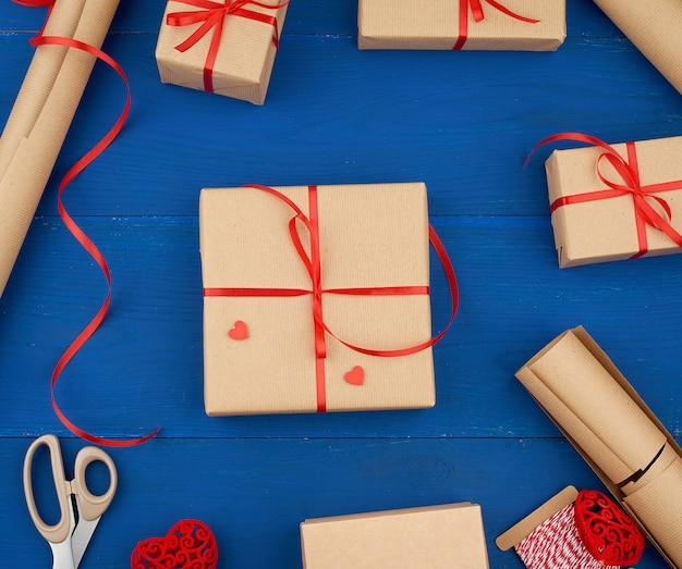 Braunes kraftpapier, verpackte geschenkbox und mit einem roten band zusammengebunden