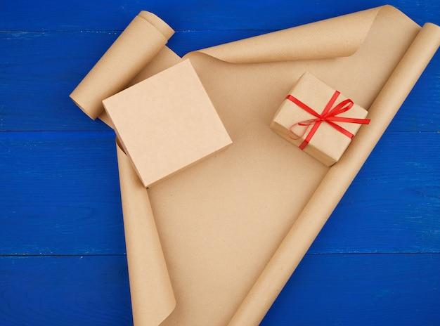 Braunes kraftpapier, verpackte geschenkboxen und mit einem roten band zusammengebunden