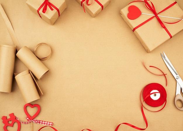 Braunes kraftpapier, verpackte geschenktüten und mit einem roten band zusammengebunden