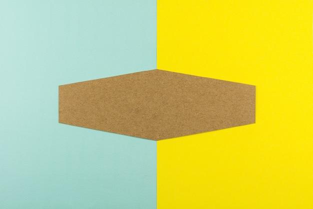 Braunes papier des hexagons auf blauem und gelbem papierhintergrund