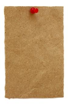 Braunes papier mit pin auf weißem hintergrund
