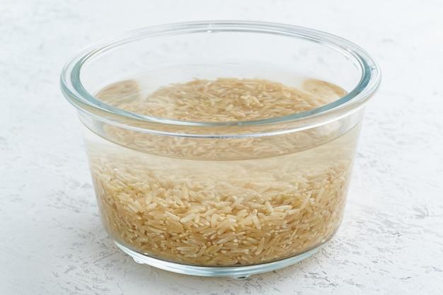 Braunes reisgetreide in wasser einweichen, um getreide zu fermentieren und phytinsäure zu neutralisieren