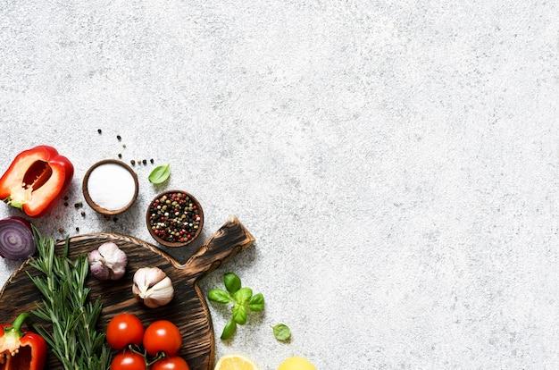 Braunes schneidebrett mit gewürzen und gemüse auf einem hellen küchentisch aus beton.