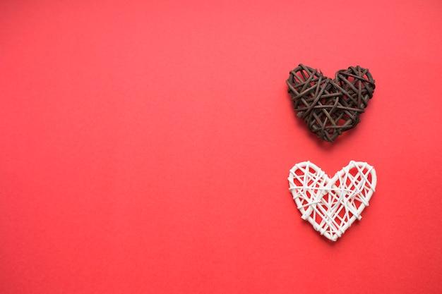 Braunes und weißes hölzernes herz auf einem roten hintergrund. liebe und valentinstag konzept. platz für text