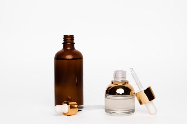 Braunglasflaschen mit pipette auf weißem hintergrund
