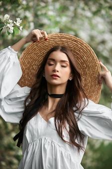 Braunhaarige frau in einem großen strohhut und einem weißen kleid posiert vor dem hintergrund blühender weißer bäume. romantischer look, natürliche schönheit, saubere gesichtshaut