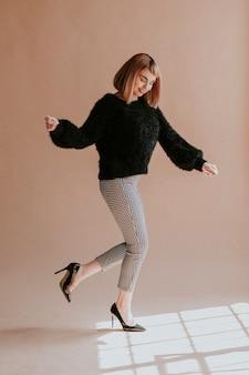 Braunhaarige frau in einem schwarzen, flauschigen pullover, der mit high heels hüpft