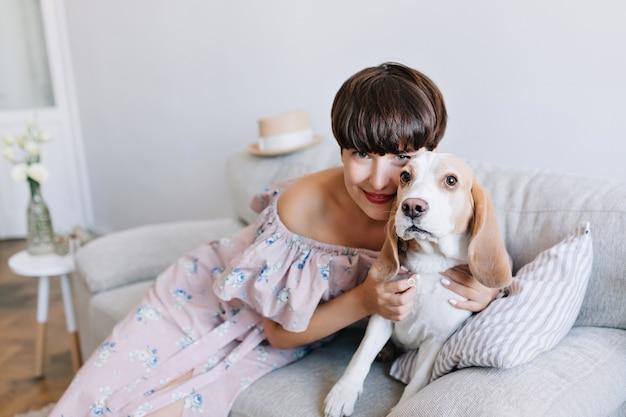 Braunhaariges lächelndes mädchen im rosa kleid, das mit ihrem niedlichen beagle-hund zu hause spielt