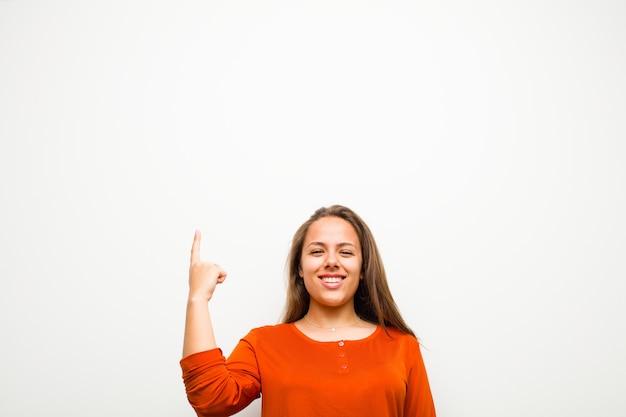 Braunhaariges mädchen, das mit einer hand lächelt und nach oben zeigt