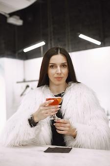 Braunhaariges mädchen. frau in einem weißen pelzmantel. roter cocktail