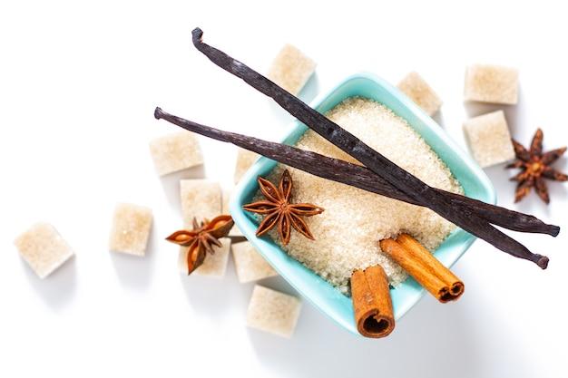 Braunzucker des lebensmittelhintergrundes, vanillehülsen, zimtstange und sternanis auf weißem hintergrund