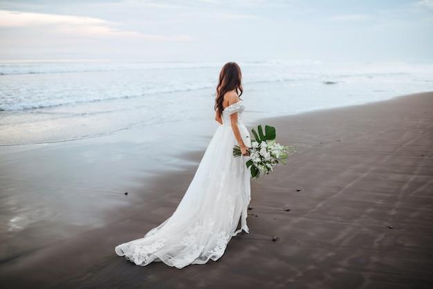 Braut am strand im blauen wasser