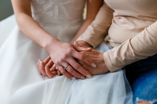 Braut an ihrem hochzeitstag hält die hände ihrer mutter