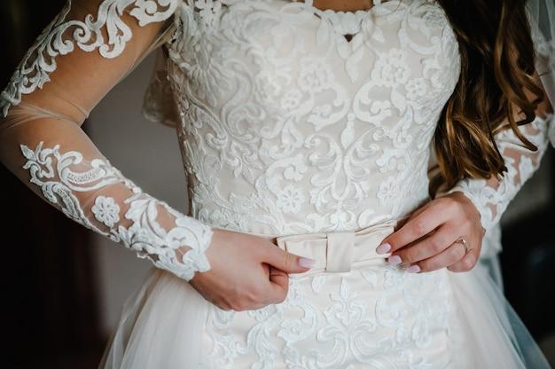 Braut befestigen gürtel nahaufnahme im hochzeitskleid und bekommen ihr kleid