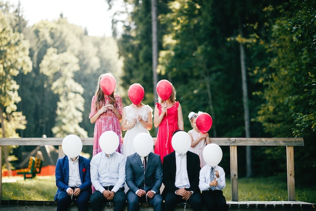 Braut, bräutigam und freunde halten luftballons im freien