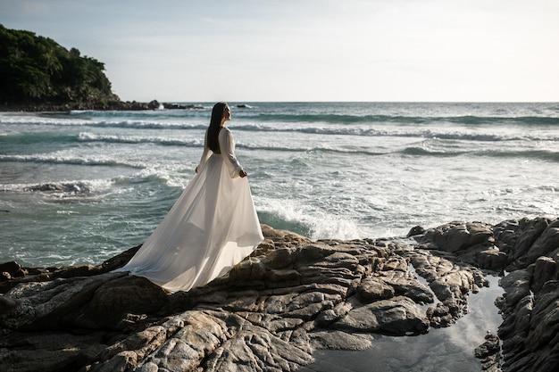 Braut, die auf dem strand in einem hochzeitskleid geht