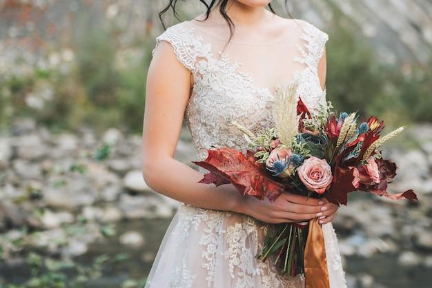Braut, die bunten eleganten modernen fallhochzeitsblumenstrauß im rot für eine herbsthochzeit hält