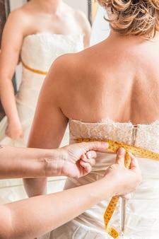 Braut, die das kleid mit der näherin probiert