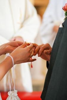 Braut, die dem bräutigam in der hochzeit ring gibt