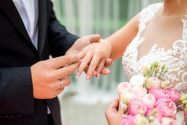 Braut, die ehering am finger des bräutigams anzieht.
