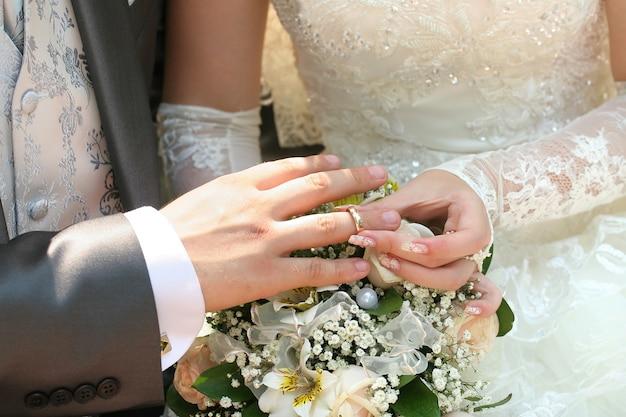 Braut, die ehering auf den finger des bräutigams legt