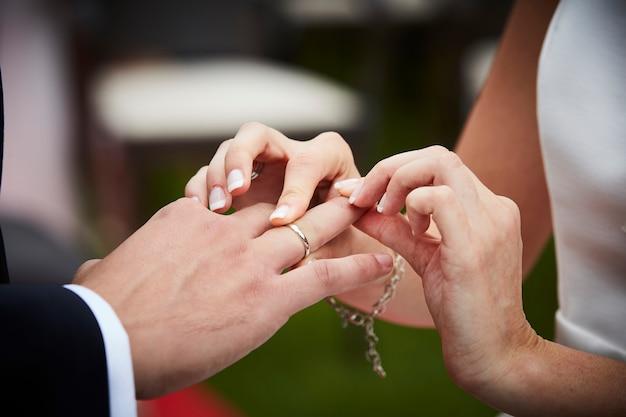 Braut, die ehering auf den finger eines bräutigams setzt