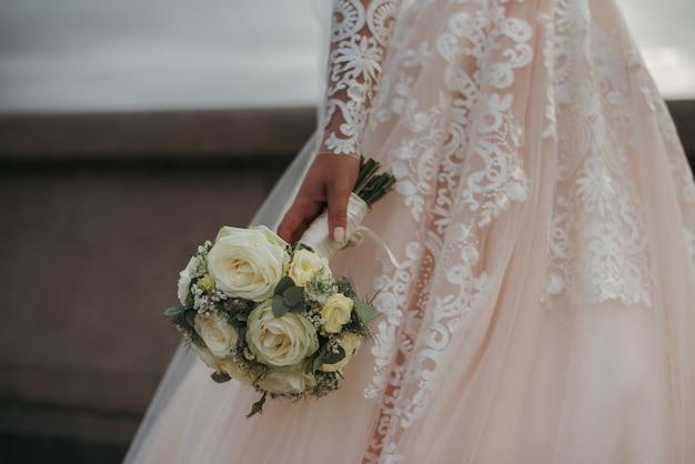 Braut, die ein schönes hochzeitskleid trägt und den blumenstrauß ihres hochzeitstags der schönen rosen hält