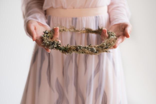 Braut, die einen blumenkranz von trockenblumen hält. weißer hintergrund im studio. morgen der braut