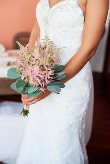 Braut, die einen blumenstrauß von blumen in einer rustikalen art, hochzeitsblumenstrauß hält
