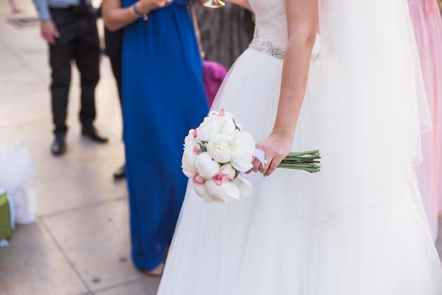 Braut, die einen blumenstrauß von weißen blumen in einer rustikalen art hält