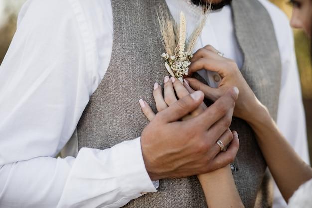 Braut, die einen boutonniere auf die stilvolle bräutigamweste setzt