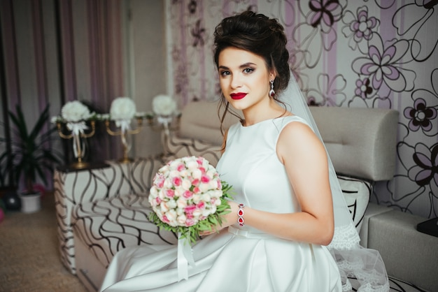 Braut, die einen brautblumenstrauß mit den kleinen gelben und rosa rosen hält und zur kamera schaut.