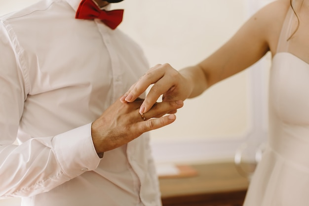 Braut, die einen ehering auf die hand des bräutigams legt