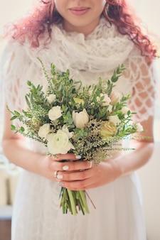 Braut, die einen hellen hochzeitsblumenstrauß mit verschiedenen blumen hält