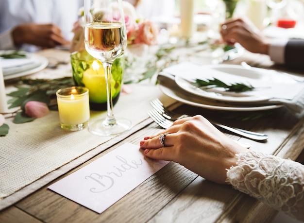 Braut, die enagaeal ring auf linker hand auf hochzeits-feier mit familie zeigt