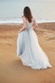 Braut, die entlang die seeküste trägt schönes hochzeitskleid geht