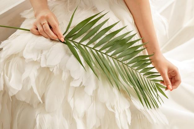 Braut, die farnblatt, rustikales oder grünes hochzeitskonzept hält.
