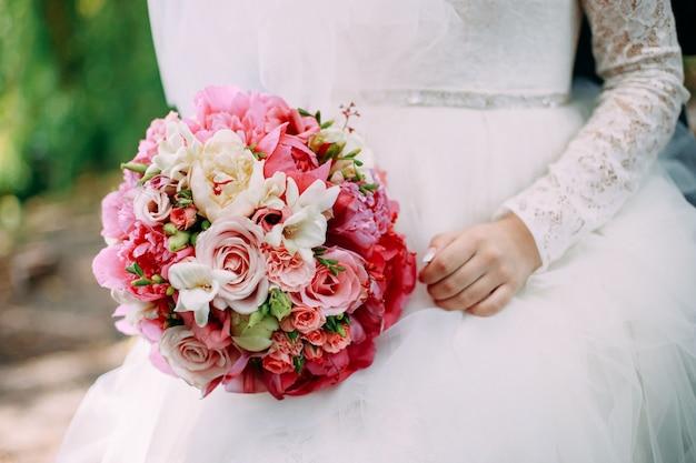 Braut, die frühlingsblumenstrauß mit rosa flowres hält