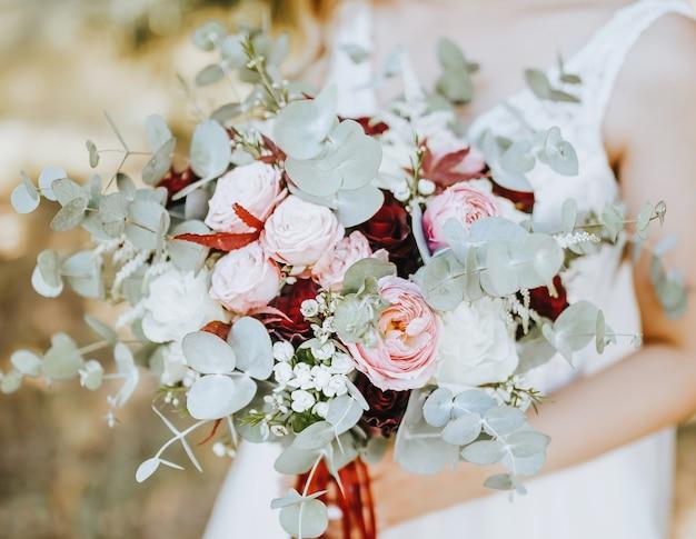Braut, die hochzeitsstrauß mit roten und rosa blumen hält