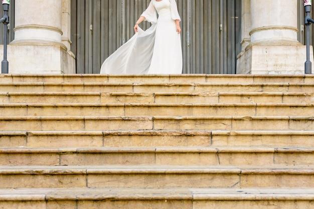 Braut, die ihr lustiges hochzeitskleid auf steintreppe wellenartig bewegt.