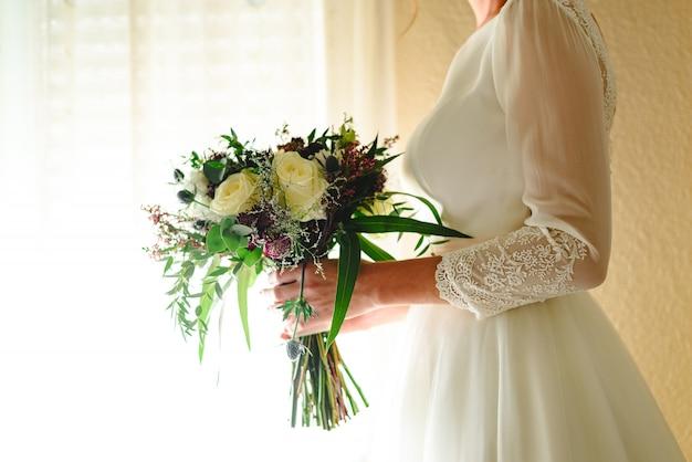 Braut, die ihren hochzeitsblumenstrauß anhält