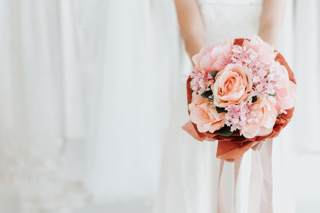 Braut, die in der hand hochzeitsblumenstrauß hält